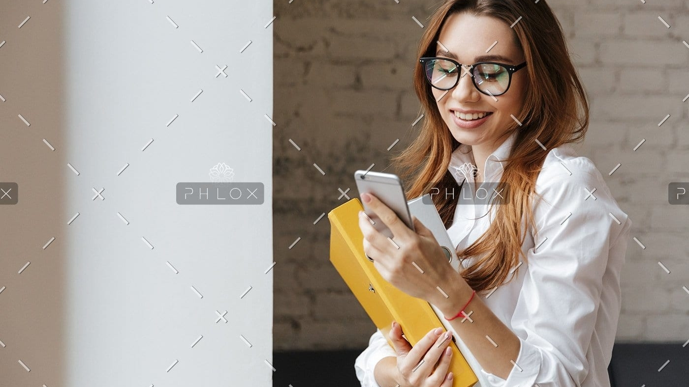 happy-business-woman-indoors-using-mobile-phone-P9WS3SD