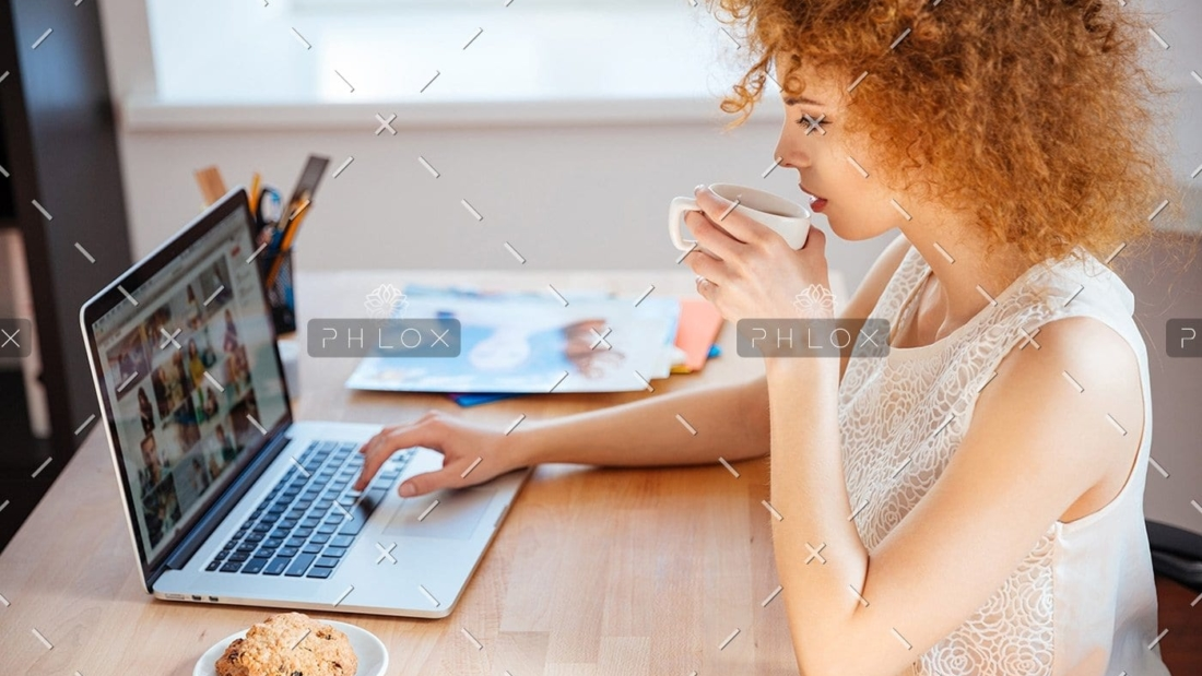 woman-photographer-drinking-coffee-and-working-PJNBP6U