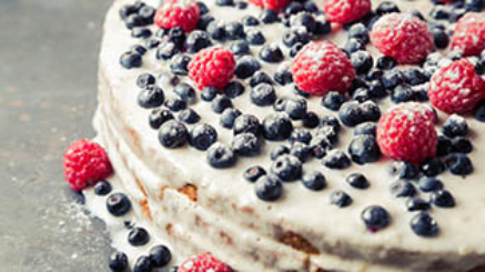 Tasty homemade cake with blueberries and raspberries on vintage grey background