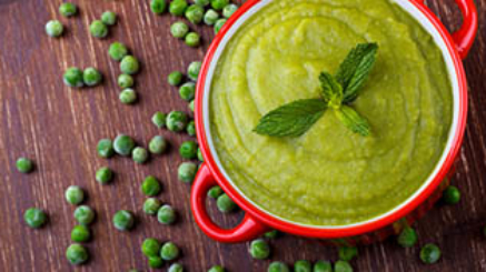 Bowl of healthy green pea soup on rustic wooden table