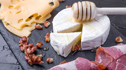 Cheese and meat plate with walnuts on black slate plate background. Camembert with honey.