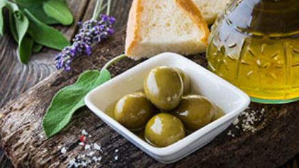 Olives and olive oil on rustic wooden background