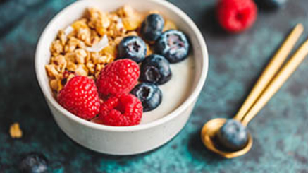 Vegetarian breakfast, a bowl with organic granola, fresh raspberries and blueberries and coconut yoghurt.